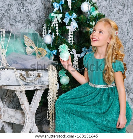 Smiling blonde girl in fashion turquoise dress sitting down by the decorated Christmas tree - stock photo