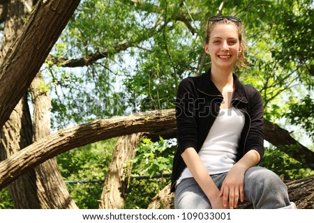 Smiling blonde girl outside in a tree