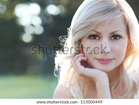 Smiling blonde girl. Portrait of happy beautiful young woman, outdoors. Copy space. Bokeh  - stock photo