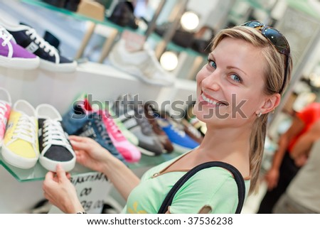 smiling blonde girl shopping for colorful sporty shoes - stock photo