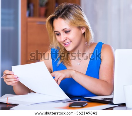 Smiling blonde girl working with documents in office