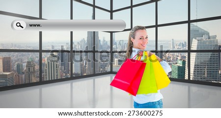 Smiling blonde holding shopping bags against room with large window showing city - stock photo