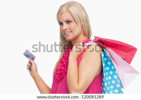 Smiling blonde holding shopping bags and credit card against white background