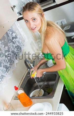 Smiling blonde housewife washing dishes in  kitchen - stock photo