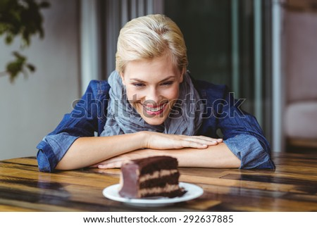 Smiling blonde looking a chocolate cake at the cafe - stock photo