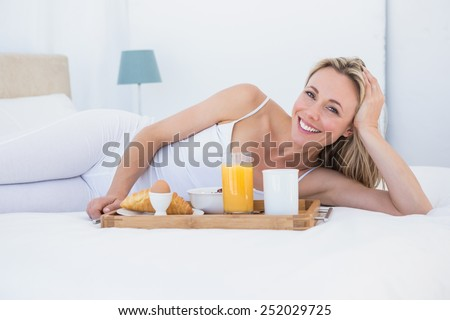 Smiling blonde lying and having breakfast in bed at home in the bedroom - stock photo