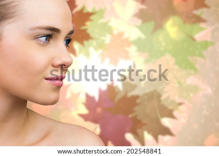 Smiling blonde natural beauty against autumnal leaf pattern in warm tones - stock photo
