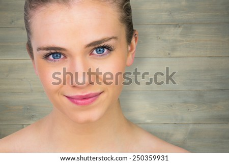 Smiling blonde natural beauty against bleached wooden planks background - stock photo