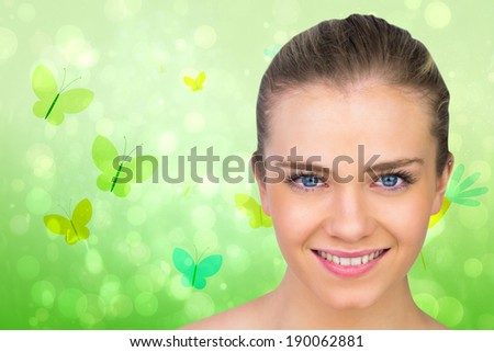Smiling blonde natural beauty against girly bird and butterfly design - stock photo