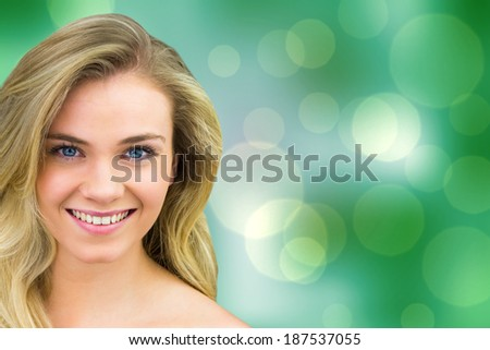 Smiling blonde natural beauty against green abstract light spot design - stock photo