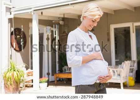 Smiling blonde pregnant handon hi belly at home - stock photo