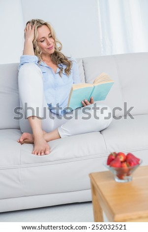 Smiling blonde reading a book on couch at home in the living room - stock photo