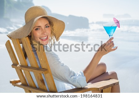 Smiling blonde relaxing in deck chair by the sea holding cocktail on a sunny day - stock photo