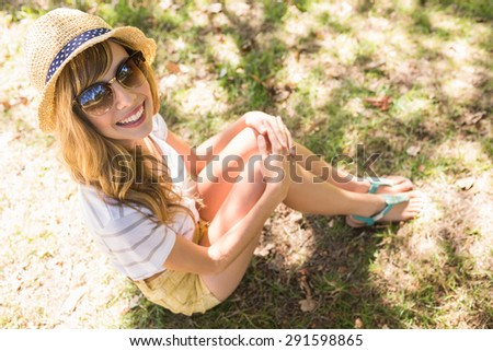 Smiling blonde relaxing in the grass on a sunny day
