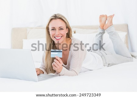 Smiling blonde shopping online on the bed in hotel room - stock photo