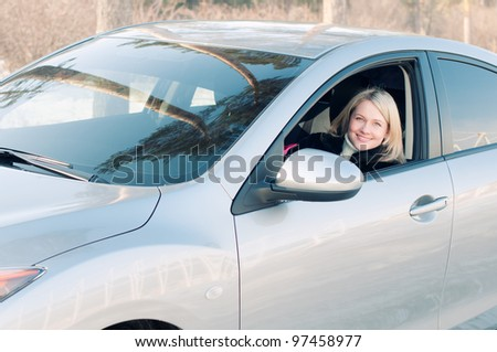 Smiling blonde sitting behind the wheel of the car on a winter road - stock photo