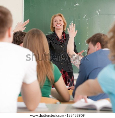 Smiling blonde teacher in a classroom - stock photo