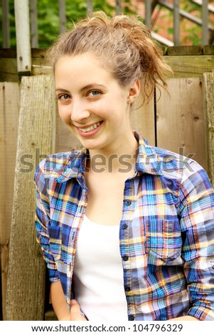 Smiling blonde teeth with checkered shirt against a fence