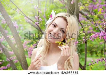 Smiling blonde woman beauty portrait, perfect fresh skin and healthy white smile, daily basic makeup, long hair with orchid flower. Outdoor in spring park