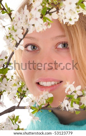 Smiling blonde woman behind spring white cherry flowers. Focus on woman's eyes. - stock photo