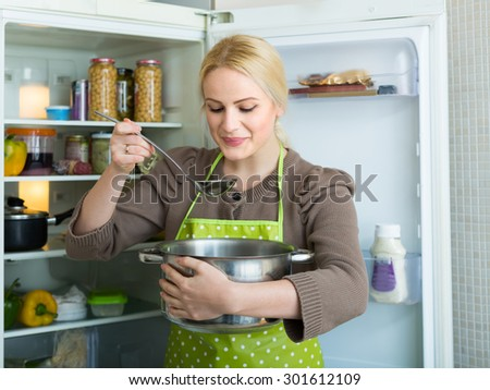 Smiling blonde woman eating soup from pan near fridge at home - stock photo