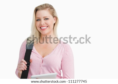 Smiling blonde woman holding a shoulder bag with a tablet pc against a white background - stock photo