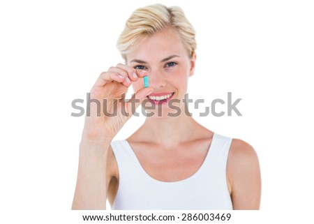 Smiling blonde woman holding blue pill on white background - stock photo