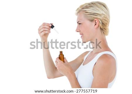 Smiling blonde woman holding bottle of medicine on white background - stock photo