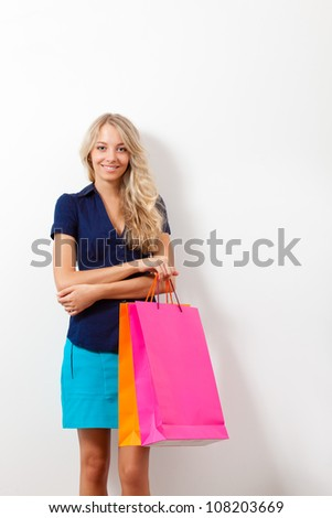 smiling blonde woman holding shopping bags near white wall, copy space - stock photo