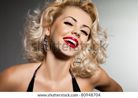 smiling blonde woman in black dress - stock photo