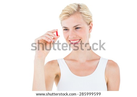 Smiling blonde woman looking at red pill on white background - stock photo