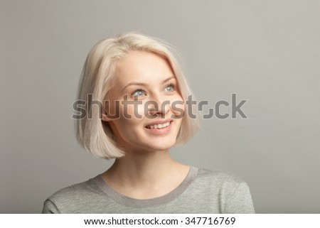 smiling blonde woman looking right on gray background - stock photo