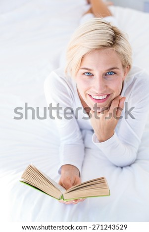 Smiling blonde woman lying on the bed and reading a book in her bedroom - stock photo