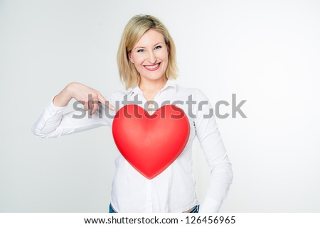 Smiling blonde woman pointing to her heart - stock photo