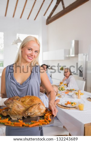 Smiling blonde woman showing the roast turkey for thanksgiving - stock photo