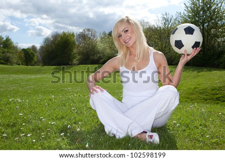 Smiling blonde woman sitting on green grass in the park about to throw a football which she is holding in her left hand - stock photo