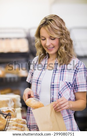 Smiling blonde woman taking a bread in a bakery - stock photo
