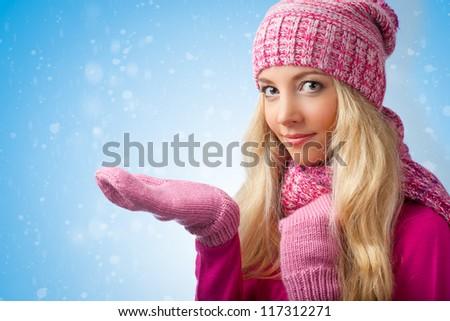 smiling blonde woman wearing pink knitwear catching snowflakes - stock photo