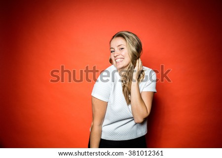 Smiling Blonde woman with grey wool jersey posing in front of orange background in studio with vibrant contrasty light - stock photo