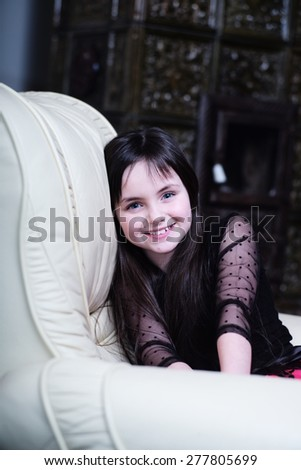 Smiling blue-eyed brunette girl sitting on the white couch, vertical picture - stock photo
