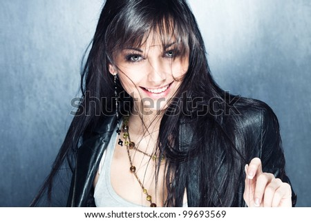 smiling blue eyes young woman with healthy and shiny long hair in black leather jacket, studio shot - stock photo