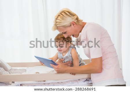 Smiling bonde woman with his son using digital tablet at home in bedroom - stock photo