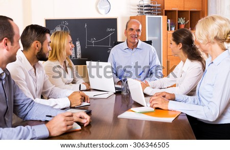 Smiling boss makes a presentation at a meeting in the office - stock photo