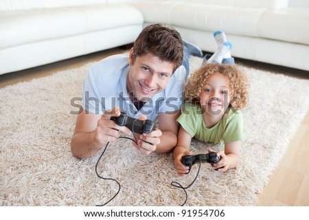Smiling boy and his father playing video games while lying on a carpet - stock photo