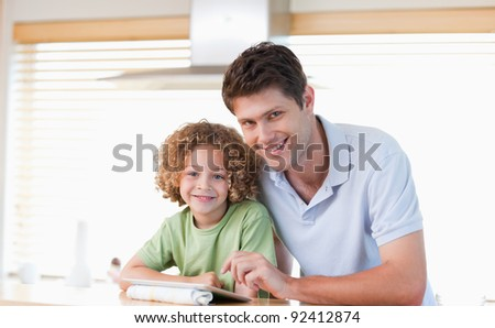 Smiling boy and his father using a tablet computer in their kitchen - stock photo