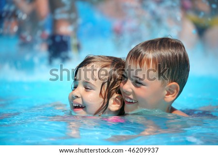 Smiling boy and little girl swimming in pool in aquapark - stock photo