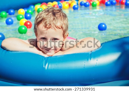 Smiling boy at swimming pool with balls - stock photo