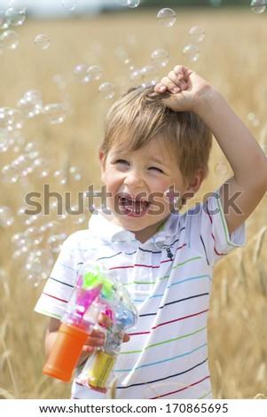Smiling boy blows bubbles - stock photo