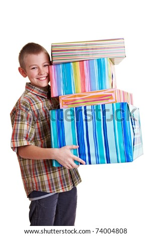 Smiling boy carrying many colorful gifts in his hands - stock photo