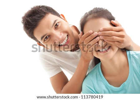 Smiling boy covering eyes of his girlfriend - stock photo